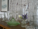 The glass jugs sit with decanters, vases and lemon juicer.